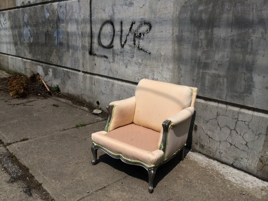 old pink chair on sidewalk with the word Love spray painted on concrete wall